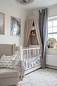 An upholstered armchair and a cot with a canopy