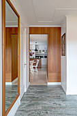 A hallway with a large wall mirror, teak panelling and a tiled floor