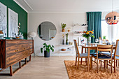 A sideboard in front of a green wall, a round mirror on the wall and an open shelf in a dining room