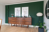 Art prints hanging above a sideboard on a green wall