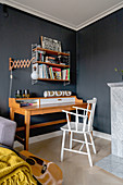 A desk and an open shelf in a guest room with a dark wall