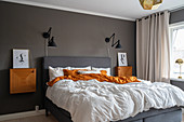 A double bed, bedside tables and wall lights in a bedroom with a dark wall