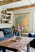 A rustic coffee table, a sofa with a blue cover and a map of Europe in a rural-style living room