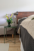 A bouquet of flowers on a bedside table next to a bed with headboard made of recycled wood