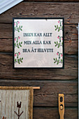 An embroidered picture with message on a rustic wooden wall