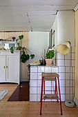 A stool and a floor lamp against a tiled wall in a kitchen