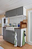 A kitchen sink unit with grey fronts