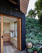 Modern extension with open façade structure and open door leading into kitchen