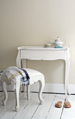 Baroque stool at console table against cream wall