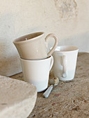 Cups in natural shades on rustic wooden surface next to stone wall