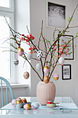 Handmade Easter eggs hung from branches in vase