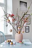 Zweige mit DIY-Ostereiern in einer Vase