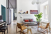 Lounge with upholstered sofa and vintage armchairs in an open living room