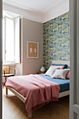 A double bed in a bedroom with wallpaper on a wall
