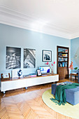 Black-and-white photos on a blue wall above a lowboard in old-style living room with a parquet floor