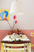 A hanging lamp above a kitchen table with garden chairs