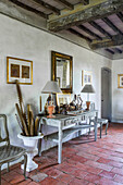 Console table with lamps in room with terracotta floor tiles and wood-beamed ceiling
