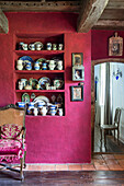 Crockery collection in niche in purple wall