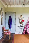 Chair in front of wooden door with bathrobe in bedroom
