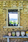 Clay pots on wooden bench against stone wall with window cut-out