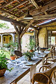 Long dining table with rattan chairs on veranda with rustic wooden roof