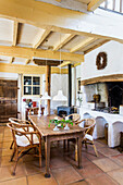 Wooden table with rattan chairs in front of wood stove in country house kitchen