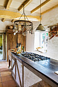Long counter with gas hob in country house kitchen with wood-beamed ceiling