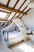 Bett mit Baldachin und Beistelltisch in ländlichem Dachzimmer mit Holzbalkendecke