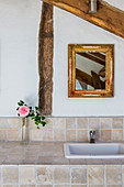 Vase with a rose on tiled washstand, in rustic attic room