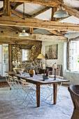 Long wooden table with metal chairs in rustic dining room with wood-beamed ceiling