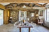 Long wooden table with metal chairs in rustic dining room with wooden beams