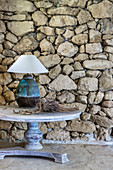 Round table with table lamp against stone wall