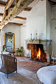 Fireplace with fire in rustic room with wooden beam ceiling