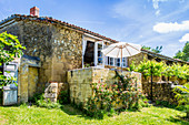 Stone house with sunny garden and parasol on terrace