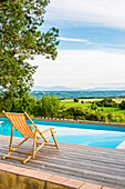 Deck chair by the pool with landscape view