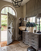 Entrance hall with flagstone flooring, large pendant light and chest of drawers