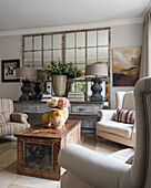 Pair of large grey lamps on large french console table in seating area with wing-back armchairs and antique chest