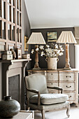 French armchair and chest of drawers by fireplace
