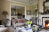 Drawing room with ottoman, chandelier and three-seater linen sofa