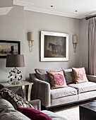 Equestrian artwork above sofa with rose cushions