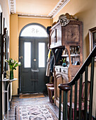Antique wooden cabinet in hallway with lettercage on back of front door