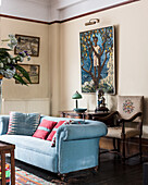 Embroidered chair-back with light blue sofa and artwork in drawing room