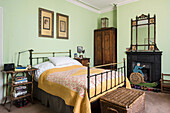 Original prints hang above French iron bed with Arts and Crafts ebonised and gilt mirror
