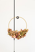 Golden ring decorated with dried hydrangeas