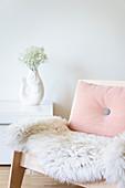 Schaffell und rosa Kissen auf einem Holzsessel vor Vase in Fischform