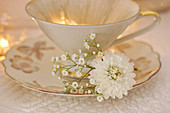 Gilt-edged china teacup with white chrysanthemum and gypsophila on saucer