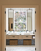 Twin sinks with swivelling mirrors in front of bathroom window