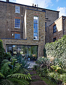 Ferns and yuccas in lush garden of brick house with extension