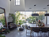 Retro dining room with glass wall overlooking garden