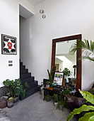 Floor-standing mirror and collection of houseplants at foot of grey staircase
